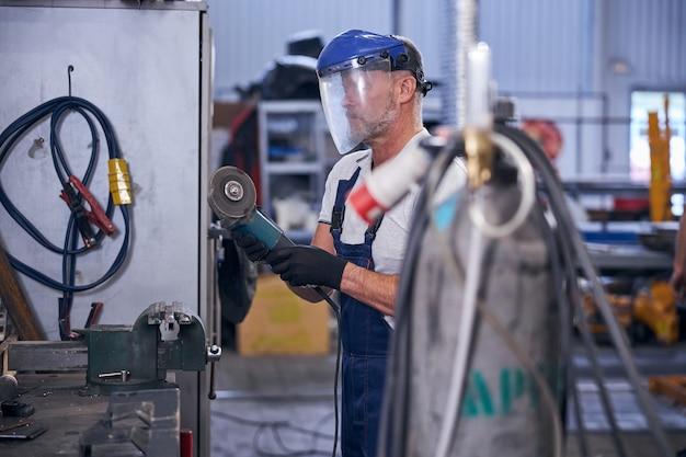 Brodaty mężczyzna używający szlifierki w garażu