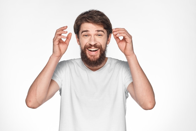Brodaty mężczyzna w białej koszulce pozuje na białej ścianie