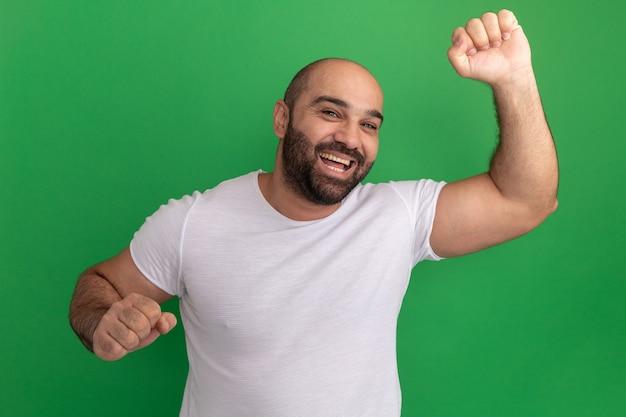 Brodaty mężczyzna w białej koszulce, szczęśliwy i podekscytowany, wznoszący pięści, stojący nad zieloną ścianą