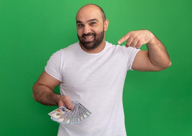 Brodaty mężczyzna w białej koszulce trzyma gotówkę szczęśliwy i pozytywny, wskazując palcem wskazującym na pieniądze stojąc nad zieloną ścianą