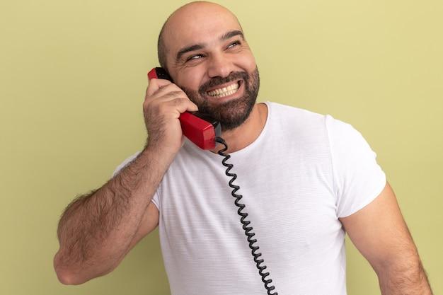 Brodaty mężczyzna w białej koszulce trzyma stary telefon patrząc na bok z uśmiechem na twarzy stojącej nad zieloną ścianą