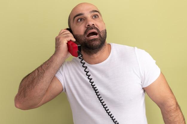 Brodaty mężczyzna w białej koszulce trzymający stary telefon patrząc zdumiony i zdziwiony stojąc nad zieloną ścianą