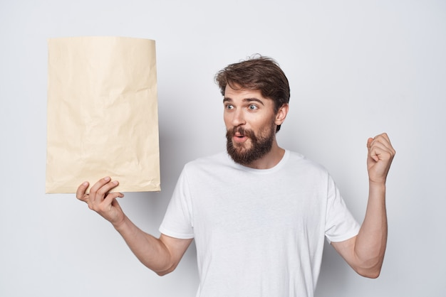 Brodaty mężczyzna w białej koszulce z torbą kraft na zakupy