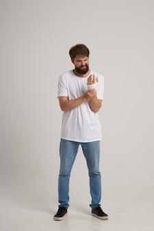 Brodaty mężczyzna w białej koszulce z zabandażowaną dłonią pozuje szpitalną medycynę