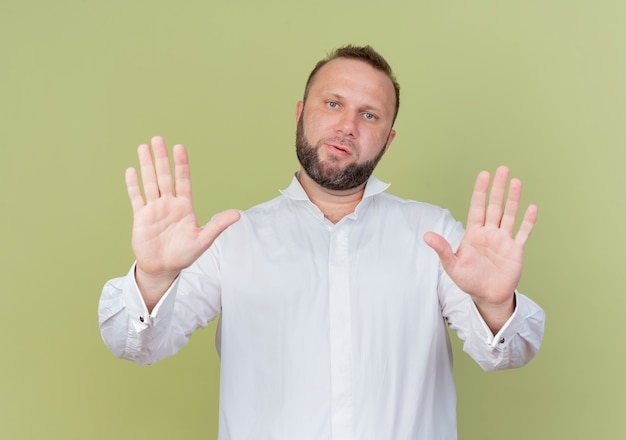 Brodaty mężczyzna w białej koszuli niezadowolony wykonując gest stopu z otwartymi dłońmi stojąc nad jasną ścianą