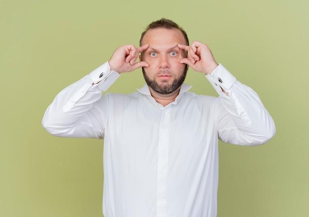 Brodaty mężczyzna w białej koszuli, otwierający oczy z palcami, próbujący lepiej widzieć stojąc nad jasną ścianą