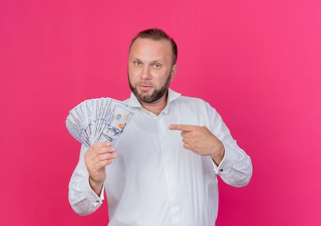 Brodaty mężczyzna w białej koszuli pokazując gotówkę wskazując palcem wskazującym na pieniądze patrząc pewnie stojąc na różowej ścianie