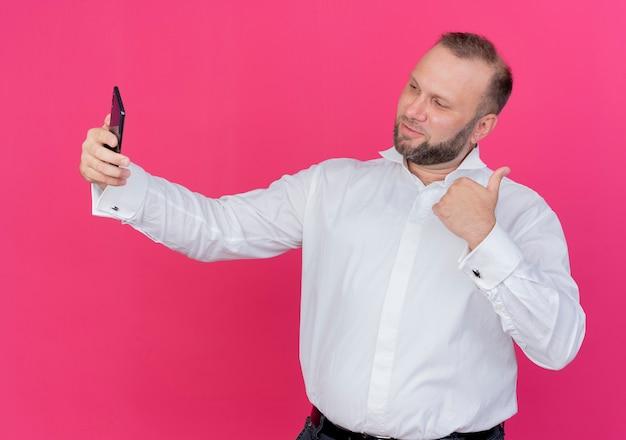 Brodaty mężczyzna w białej koszuli robi selfie pokazując kciuki do góry stojąc na różowej ścianie