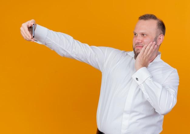 Brodaty mężczyzna w białej koszuli robi selfie uśmiechając się z szczęśliwą twarzą stojącą nad pomarańczową ścianą