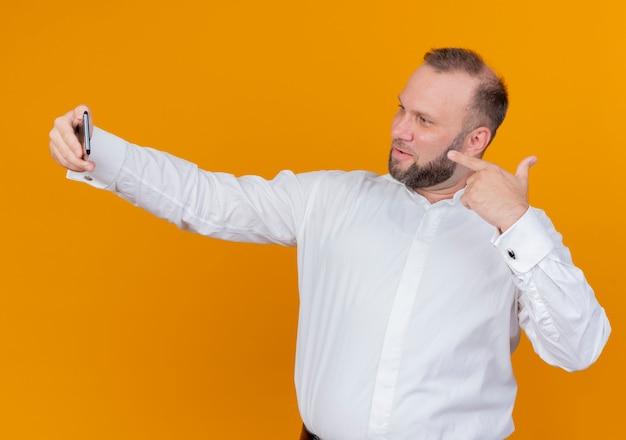 Brodaty mężczyzna w białej koszuli robi selfie uśmiechnięty stojący nad pomarańczową ścianą