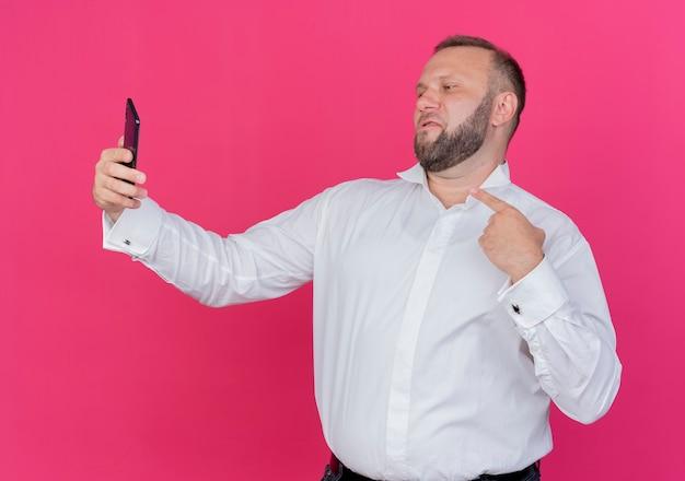 Brodaty mężczyzna w białej koszuli robi selfie, wskazując palcem stojącym na różowej ścianie