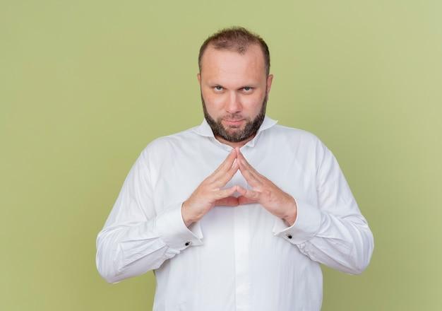 Brodaty mężczyzna w białej koszuli trzymając dłonie razem, czekając z poważną twarzą stojącą nad jasną ścianą