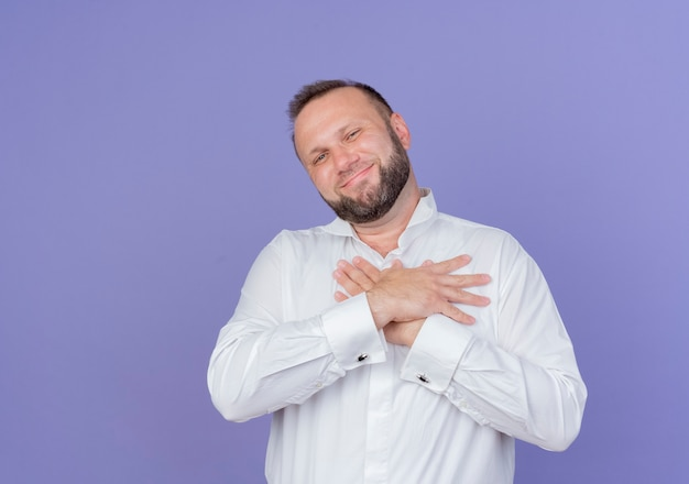 Brodaty mężczyzna w białej koszuli, trzymając się za ręce na piersi, czuje się wdzięczny, uśmiechając się ze szczęśliwą twarzą stojącą nad niebieską ścianą
