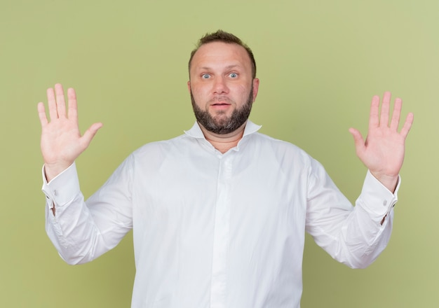 Brodaty mężczyzna w białej koszuli unoszący dłonie w geście poddania się, zdezorientowany, stojąc nad jasną ścianą