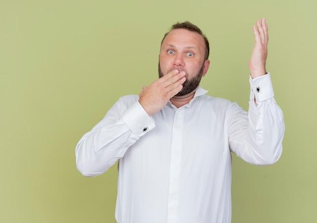 Brodaty mężczyzna w białej koszuli wygląda na zaskoczonego i zdumionego, zakrywającego usta ręką stojącą nad jasną ścianą