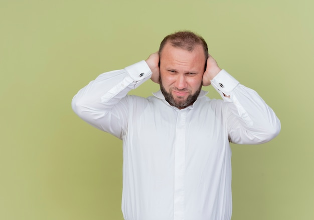 Brodaty mężczyzna w białej koszuli wygląda na zdezorientowanego zamykając uszy rękami stojącymi nad jasną ścianą