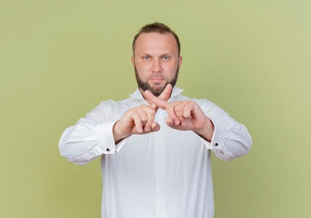 Brodaty mężczyzna w białej koszuli z poważną twarzą krzyżującą palce wskazujące stojąc nad jasną ścianą