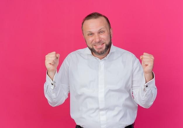 Brodaty mężczyzna w białej koszuli zaciskając pięści z radością i podekscytowaniem, stojący nad różową ścianą