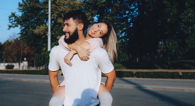 Brodaty mężczyzna w białych ubraniach niosący swoją dziewczynę i uśmiechający się na ulicy