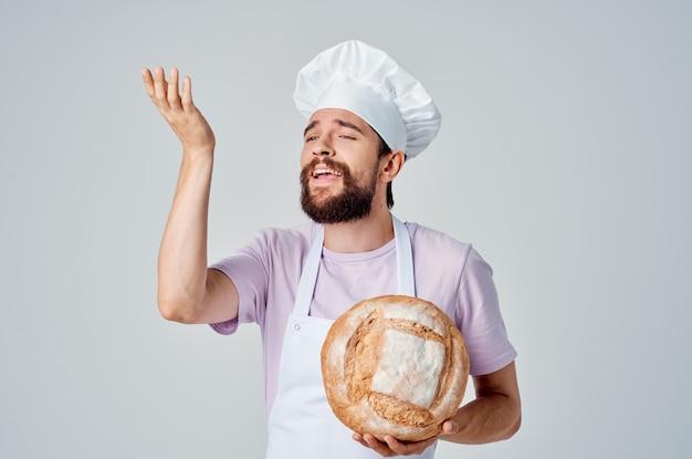 Brodaty mężczyzna w białym fartuchu gotuje jedzenie