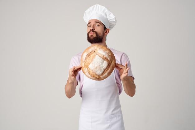 Brodaty mężczyzna w białym fartuchu z chlebem w dłoniach piecze jasne tło