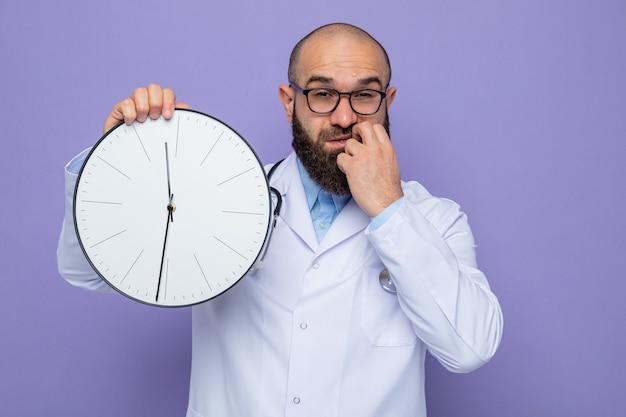 Brodaty mężczyzna w białym fartuchu ze stetoskopem na szyi trzymający zegar patrzący z zakłopotaną miną