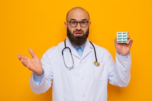 Brodaty mężczyzna w białym fartuchu, ze stetoskopem na szyi, w okularach, trzymający blister z pigułkami, wyglądający na szczęśliwego i zdziwionego unoszącego ramię