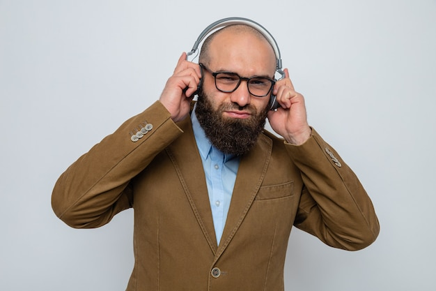 Brodaty mężczyzna w brązowym garniturze, w okularach i słuchawkach, patrzący uśmiechnięty, cieszący się muzyką