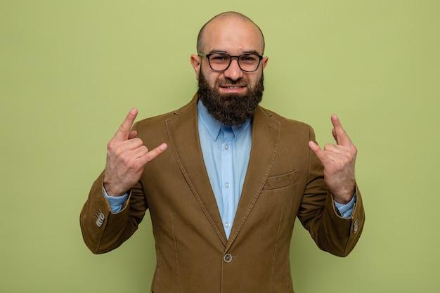 Brodaty mężczyzna w brązowym garniturze w okularach, patrząc na kamerę, uśmiechający się pewnie pokazując symbol rocka stojący nad zielonym tłem