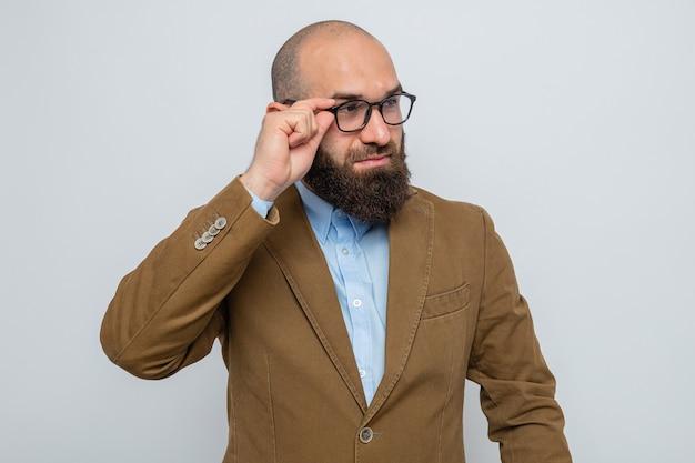 Brodaty mężczyzna w brązowym garniturze, w okularach, patrzący na bok z pewnym siebie wyrazem twarzy, stojący na białym tle