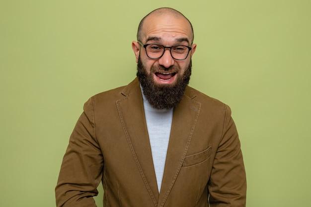 Brodaty mężczyzna w brązowym garniturze w okularach, patrzący na kamerę wesoły i wesoły uśmiechający się szeroko stojący nad zielonym tłem
