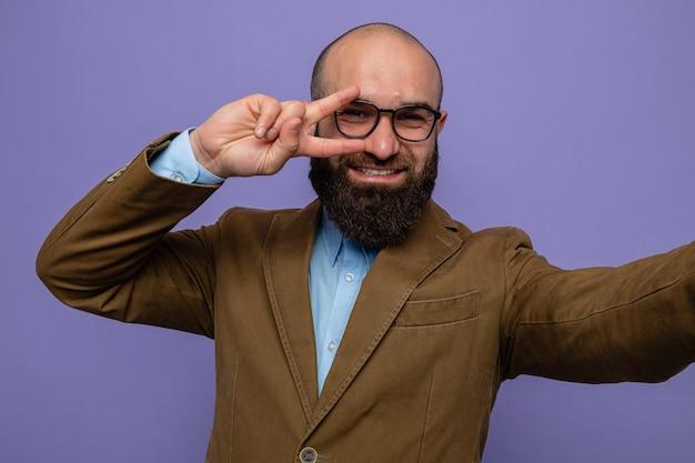 Brodaty mężczyzna w brązowym garniturze w okularach patrzący na selfie uśmiechający się radośnie pokazując znak v nad oczami