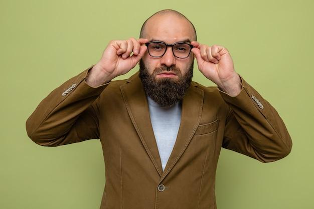 Brodaty mężczyzna w brązowym garniturze w okularach, patrzący z bliska, dotykając swoich okularów