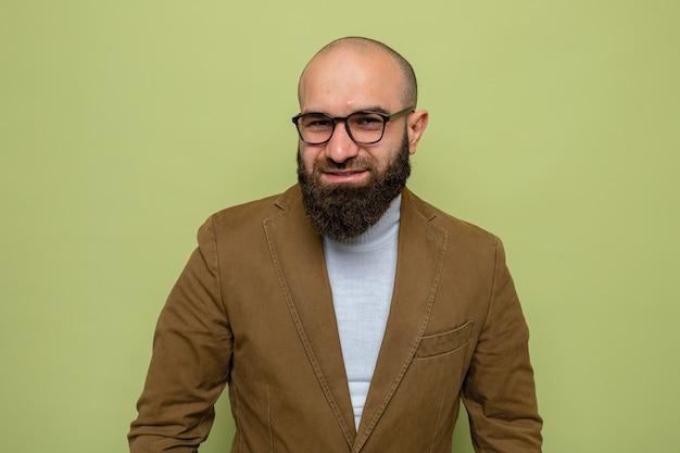 Brodaty mężczyzna w brązowym garniturze w okularach, patrzący z uśmiechem na szczęśliwą twarz