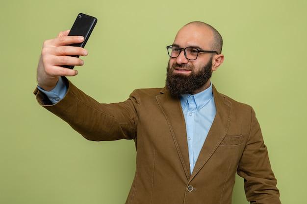 Brodaty mężczyzna w brązowym garniturze w okularach robi selfie za pomocą smartfona, uśmiechając się radośnie, stojąc na zielonym tle