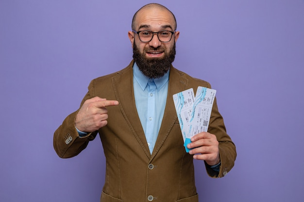 Brodaty mężczyzna w brązowym garniturze, w okularach, trzymający bilety lotnicze, wskazujący palcem wskazującym na nich, uśmiechający się radośnie, szczęśliwy i pozytywny