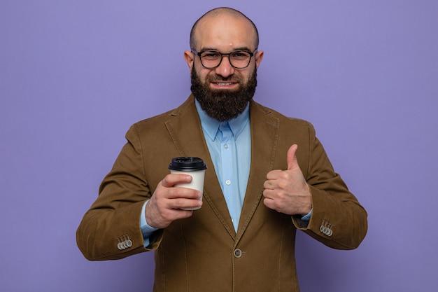 Brodaty mężczyzna w brązowym garniturze w okularach, trzymający filiżankę kawy, patrzący uśmiechnięty radośnie pokazując kciuk do góry