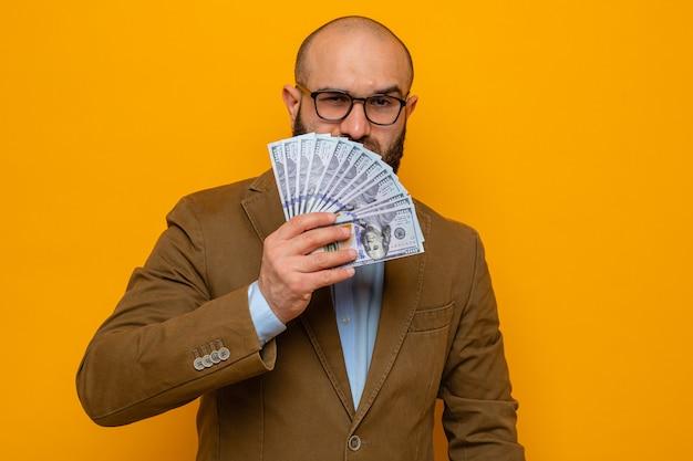 Brodaty mężczyzna w brązowym garniturze, w okularach, trzymający gotówkę, patrzący z poważnym, pewnym siebie wyrazem twarzy