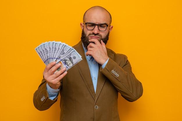 Brodaty mężczyzna w brązowym garniturze, w okularach, trzymający gotówkę, wyglądający na zdziwionego, z ręką na brodzie
