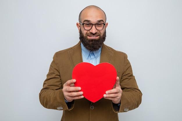 Brodaty mężczyzna w brązowym garniturze, w okularach, trzymający serce z tektury, wyglądający uśmiechnięty, radośnie szczęśliwy i pozytywny