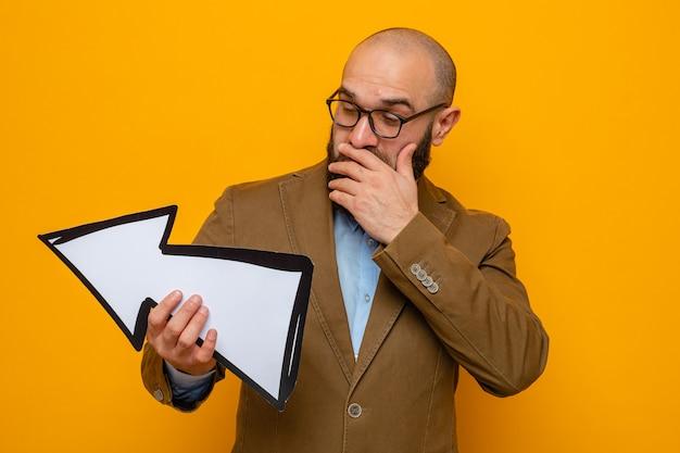 Brodaty mężczyzna w brązowym garniturze, w okularach, trzymający strzałę, patrzący na nią z zamyślonym wyrazem twarzy, stojący na pomarańczowym tle