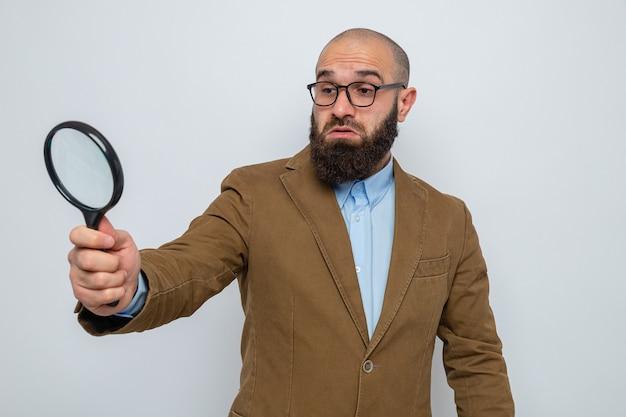 Brodaty mężczyzna w brązowym garniturze, w okularach, trzymający szkło powiększające, patrząc przez nie zdezorientowany, stojący na białym tle