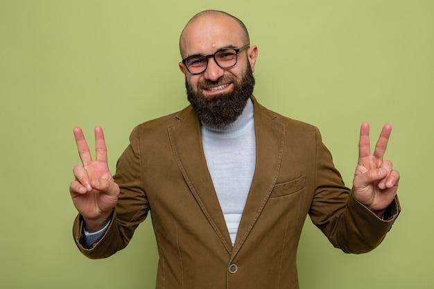 Brodaty mężczyzna w brązowym garniturze w okularach, uśmiechający się radośnie, pokazując znak v v