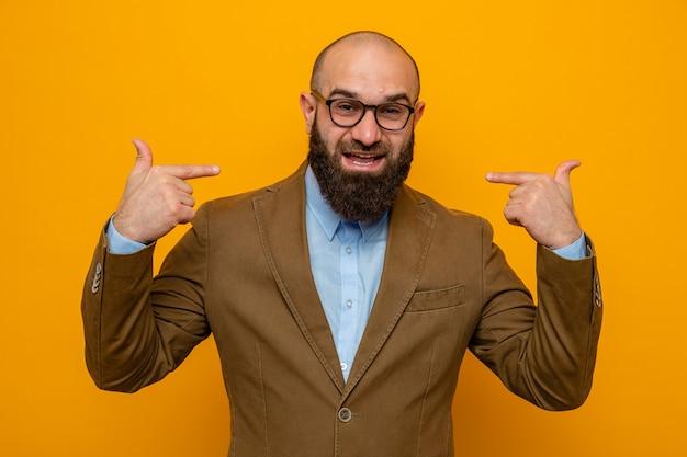 Brodaty mężczyzna w brązowym garniturze w okularach wygląda na szczęśliwego i pozytywnie wskazującego na siebie