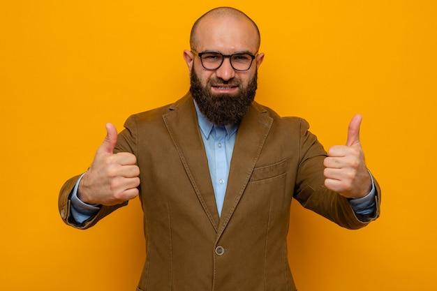 Brodaty mężczyzna w brązowym garniturze, w okularach, wyglądający na szczęśliwego i wesołego, uśmiechający się szeroko pokazując kciuk w górę