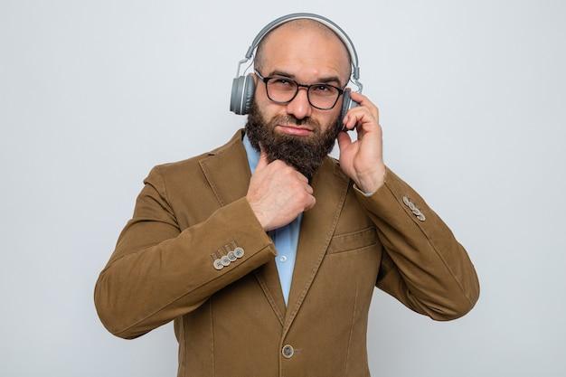 Brodaty mężczyzna w brązowym garniturze, w okularach ze słuchawkami, patrzący z zamyśloną miną