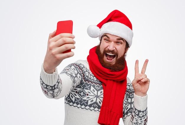 Brodaty mężczyzna w czapce świętego mikołaja, wskazując na znak pokoju i biorąc selfie