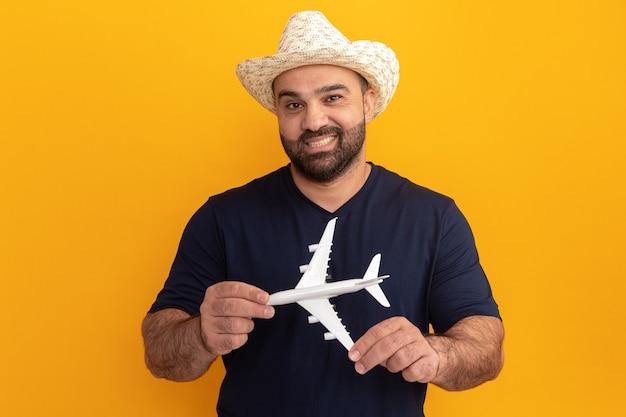 Brodaty mężczyzna w czarnej koszulce i letnim kapeluszu, trzymając zabawkowy samolot, uśmiechając się ze szczęśliwą twarzą stojącą nad pomarańczową ścianą
