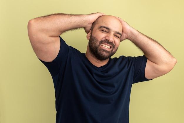 Brodaty mężczyzna w czarnej koszulce wyglądający na zirytowanego z rękami na głowie stojącego nad zieloną ścianą
