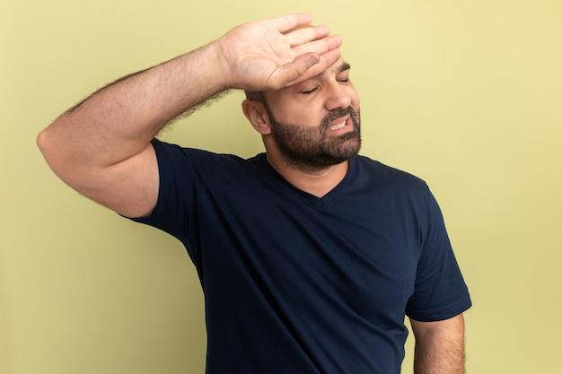 Brodaty mężczyzna w czarnej koszulce wyglądający na zmęczonego i zirytowanego, stojącego nad zieloną ścianą, z ręką na czole